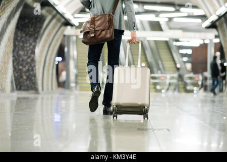 Businessman in front of escalators on a metro station. - Stock Photo