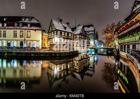 Old timber-framing houses in Petite France quarter, Strasbourg. Snow-covered roofs and refctions in the river water. - Stock Photo