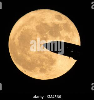 An aircraft taking off from Ronald Reagan National Airport is silhouetted by the rising super moon rises December - Stock Photo