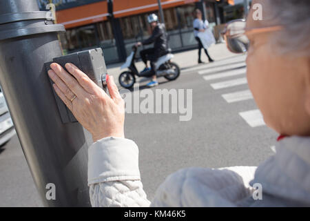 elderly woman crossing the road - Stock Photo