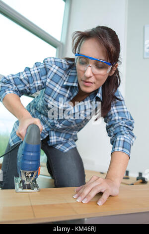 woman cutting a plank using an electric cutter - Stock Photo