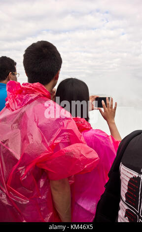 Young Asian couple in Niagara Falls Canada taking cell phone photos of the Horseshoe Falls. Tourists. - Stock Photo