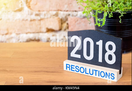 New year 2018 resolutions on blackboard sign and green plant on wood table at brick wall. - Stock Photo