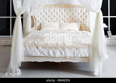 Bedroom in soft light colors. Big comfortable four poster double bed in elegant classic bedroom. Luxury white with - Stock Photo