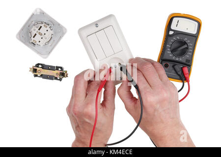 An elderly household electrician checks the isolation of the light switch using a multimeter. Isolated on white - Stock Photo