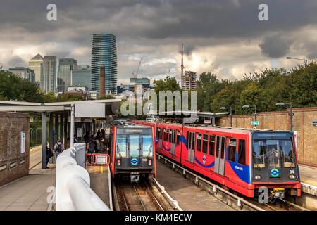 Rail Passengers board a Dockland's Light Railway Train at Mudchute DLR Station with the towers of Canary Wharf in - Stock Photo