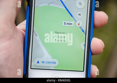 Close up view of a hand holding an iPhone with the Google Maps app active and showing Berkeley Square Gardens in - Stock Photo