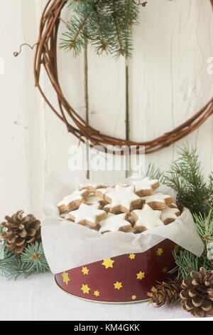 Cookies cinnamon star in a tin box on a background of fir branches and cones. - Stock Photo