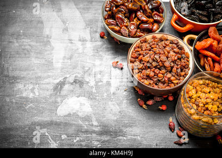 Dried fruits in bowls. On a black chalkboard. - Stock Photo