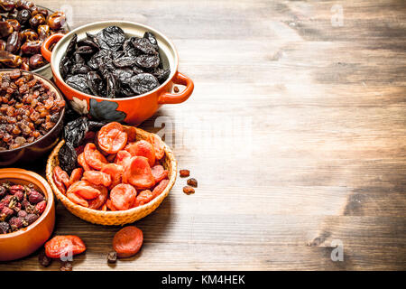 Dried fruits in bowls. On a wooden table. - Stock Photo