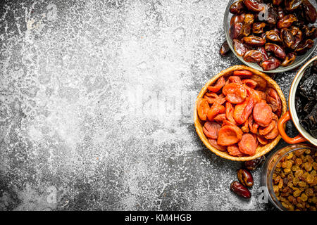 Various dried fruit in bowls. On rustic background . - Stock Photo