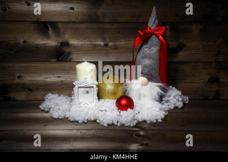 Christmas decoration with candle, picture frame, balls, snow & scandinavian gnome tomte, nisse, tomtenisse, tonttu - Stock Photo
