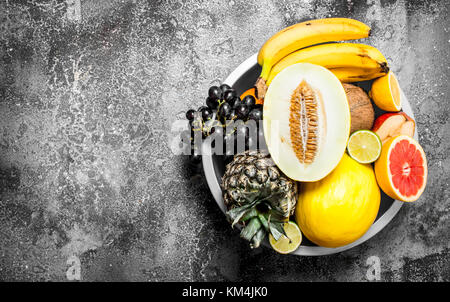 Many different fruits in a large bowl. On rustic background . - Stock Photo