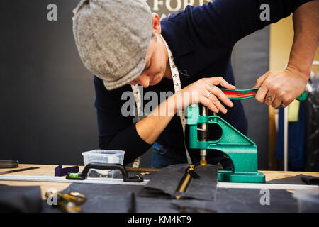 A man using a rivet machine, pressing hard on the handle at a workbench. - Stock Photo