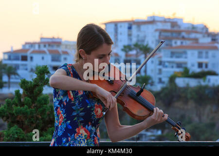A beautiful young lady playing the violin at the Balcon de Europa in Nerja on the Costa del Sol in Spain - Stock Photo