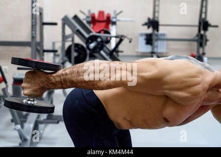 Male athlete doing deltoid exercise with dumbbells - Stock Photo