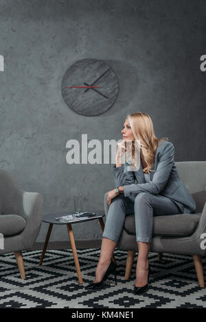 thoughtful mature businesswoman sitting on armchair in waiting room at modern office - Stock Photo