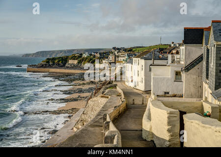 A view down the walkway on top of the seawall protection at Porthleven Cornwall, the low afternoon sun highlights - Stock Photo