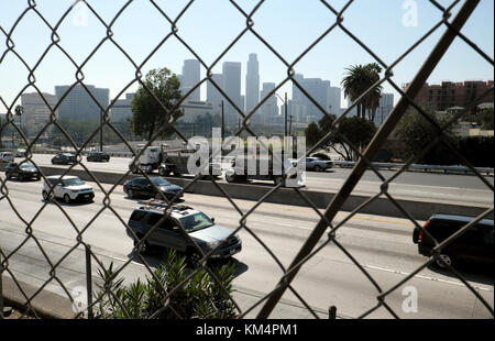 A view of downtown LA and traffic on the Hollywood Freeway looking through a fence from Echo Park Los Angeles, California - Stock Photo