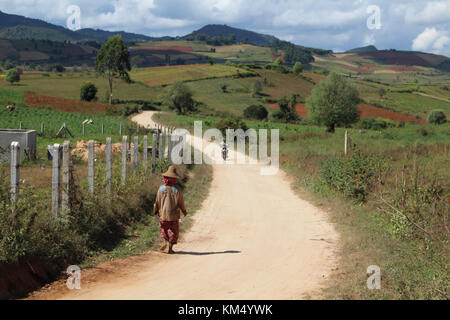 A Landscape Image of a Local Woman in Traditional Dress Walking away from camera on a dusty gravel road in Myanmar. - Stock Photo