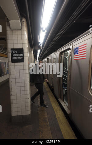 F train pulling into the station platform at the Fort Hamilton Parkway Stop in the Windsor Terrace neighborhood - Stock Photo