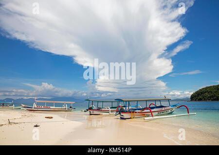 Outrigger tourist boats on idyllic tropical beach of the islet Gili Nanggu, part of the Gili Islands, island Lombok, - Stock Photo