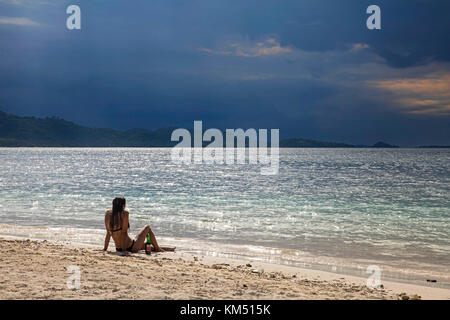 Female tourist in bikini sitting on tropical beach of the islet Gili Kedis and watching approaching thunderstorm - Stock Photo