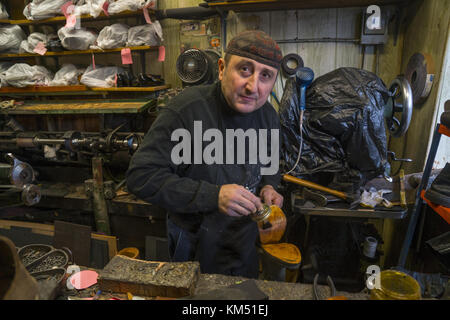 Cobbler glueing new soles on a pair of shoes in his shop in the Windsor Terrace neighborhood of Brooklyn, NY. - Stock Photo