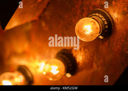 Burning light bulbs on the wall - Stock Photo