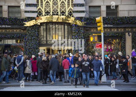 Crowds of people shopping and viewing the Christmas holiday windows at Saks Fifth Avenue on 5th Avenue at the start - Stock Photo
