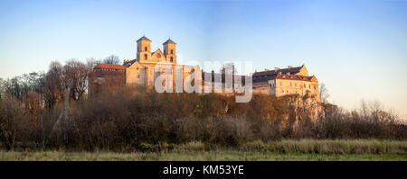 Tyniec near Krakow, Poland. Benedictine abbey on the rocky cliff in late fall  Wide panorama in sunset light - Stock Photo