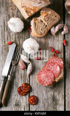 Top view on set of salami sausages with fresh bread, garlic and red hot chili peppers served with vintage tableware - Stock Photo