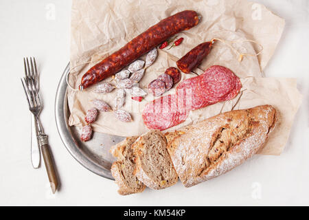 Top view on vintage tray with set of salami with fresh bread and red hot chili peppers served with vintage tableware - Stock Photo