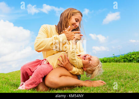 Happy family on green grass lawn. Child have fun on outside walk - mother tickling funny baby son lying on her laps. - Stock Photo