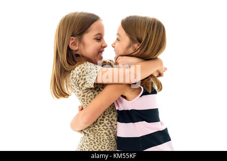 Identical twin girls are looking at each other and smiling. Concept of family and sisterly love. Profile side view - Stock Photo