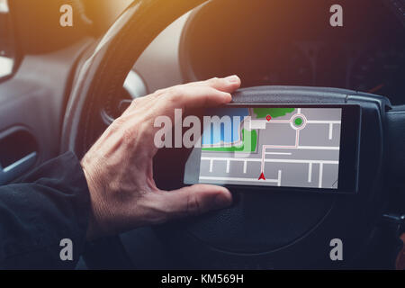 Man using GPS navigation on mobile phone in the car while driving - Stock Photo