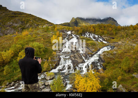 Tourist photographing Lofoten waterfall with a mobile phone in Norway - Stock Photo