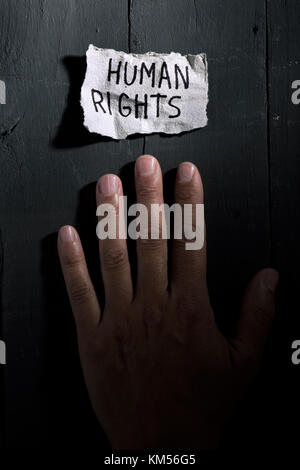 closeup of the hand of a young man and a piece of paper with the text human rights written in it on a rustic background - Stock Photo