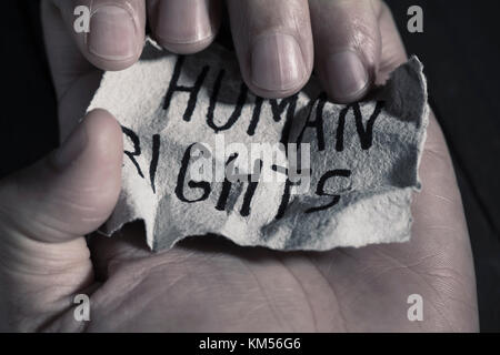 closeup of the hand of a young man with a piece of paper with the text human rights written in it - Stock Photo