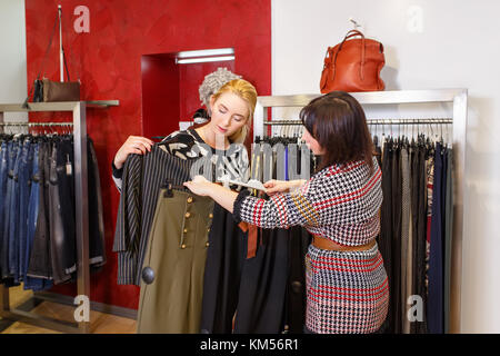 stylist helping chooses clothes for the customer - Stock Photo