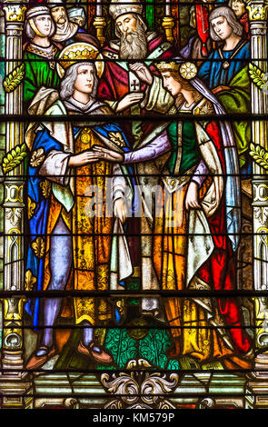 New Orleans, Louisiana - February 6, 2017: Religious colorful stained glass window depicting a wedding in St Louis - Stock Photo