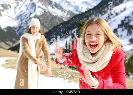 Two friends joking throwing snowballs on holidays in a snowy mountain in winter - Stock Photo