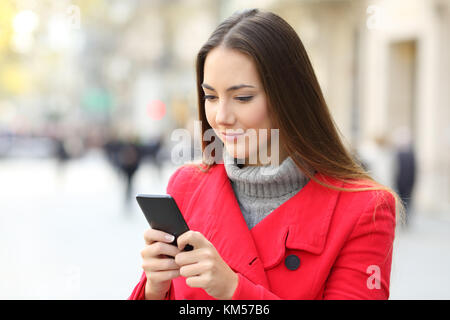 Serious woman using a smart phone standing on the street in winter - Stock Photo