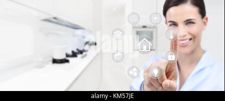smart home automation smiling woman hand touch screen with white symbols on kitchen background web banner and copy - Stock Photo