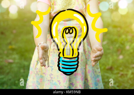 Child holding a light bulb drawing as idea concept, outdoors on a sunny day.