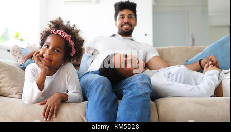 Young girl watching tv with her parents - Stock Photo