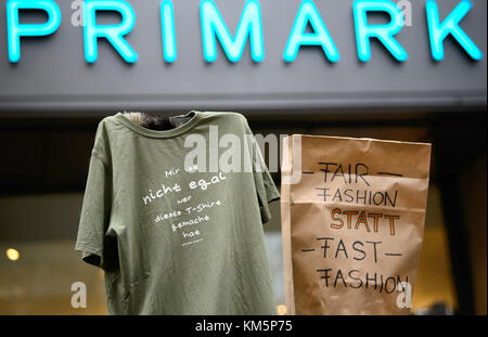 Stuttgart, Germany. 5th Dec, 2017. Protestors hold up a T-shirt with the lettering 'I do care who manufactured this - Stock Photo