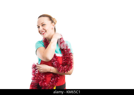 Happy wife dancing wearing a Christmas red apron and tinsel or garland isolated on white background - Stock Photo