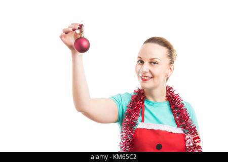 Happy housemaid wearing red apron and garland or tinsel holding a Christmas globe isolated on white background - Stock Photo