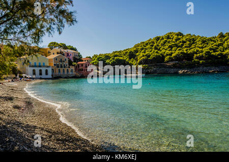 end of the picturesque bay of assos beach and colorful houses on the coast, anchored sailboat and start of the mountain - Stock Photo